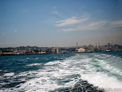 View of Eminonu coast, Beyazit Tower, Yeni Cami (Mosque) and Suleymaniye Mosque from the sea in Istanbul city of Turkey.
