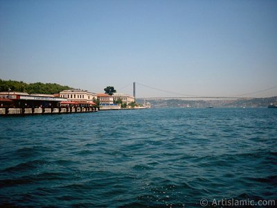 View of the Ciragan Palace and the Bosphorus Bridge from the shore of Besiktas district of Istanbul city in Turkey. (The picture was taken by Artislamic.com in 2004.)