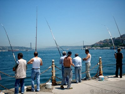 View of fishing people and on the horizon Bosphorus Bridge from Uskudar shore of Istanbul city of Turkey.