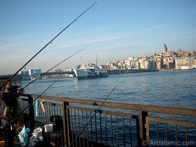 View of fishing people, a landing ship, Galata Bridge and Galata Tower from the shore of Eminonu in Istanbul city of Turkey. (The picture was taken by Artislamic.com in 2004.)