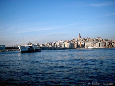 View of a landing ship, Galata Bridge and Galata Tower from the shore of Eminonu in Istanbul city of Turkey.