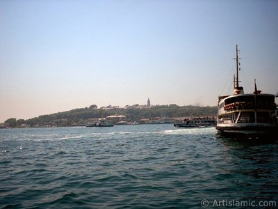 View of a ship waiting at Karakoy jetty and Topkapi Palace from the shore of Karakoy in Istanbul city of Turkey. (The picture was taken by Artislamic.com in 2004.)