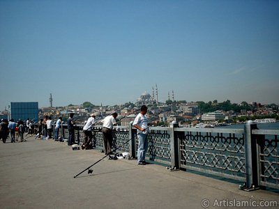 View of fishing people, on the horizon Beyazit Tower and Suleymaniye Mosque from Galata Bridge located in Istanbul city of Turkey. (The picture was taken by Artislamic.com in 2004.)