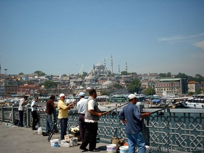 View of fishing people, at far behind Suleymaniye Mosque and below Rustem Pasha Mosque from Galata Bridge located in Istanbul city of Turkey.