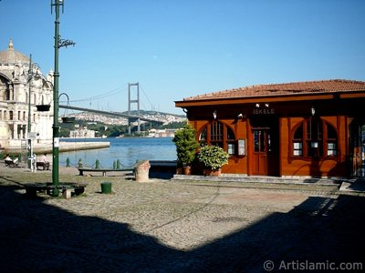 View of the jetty, Bosphorus Bridge, Ortakoy Mosque and the moon seen in daytime over the bridge`s legs from Ortakoy shore in Istanbul city of Turkey.