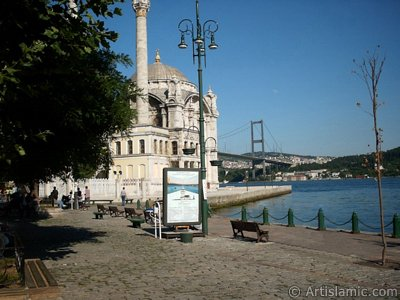 View of Bosphorus Bridge, Ortakoy Mosque and the moon seen in daytime over the bridge`s legs from Ortakoy shore in Istanbul city of Turkey. (The picture was taken by Artislamic.com in 2004.)
