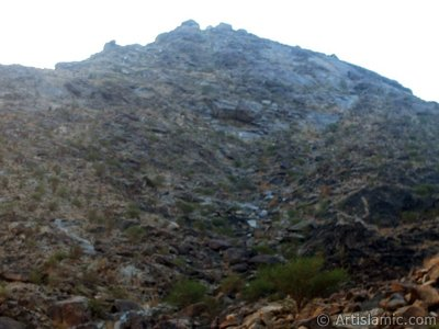 The Mount Savr in Mecca city of Saudi Arabia. The Prophet Muhammed (saaw) and his friend Abu Bakr (ra) had got shut of the Meccan enemies tracking them by hidding three days in a cave in this mount with the great help of Allah (swt). In the Holy Koran our Lord Allah said about the Savr Cave in this mount: ``If ye help not (Muhammad), (it is no matter): for Allah did indeed help him, when the unbelievers drove him out: he had no more than one companion: they two were in the Cave, and he said to his companion, ``Have no fear for Allah is with us``: then Allah sent down His peace upon him, and strengthened him with forces which ye saw not, and humbled to the depths the word of the unbelievers. But the word of Allah is exalted to the heights: for Allah is Exalted in might, Wise.`` (The Holy Koran 9:40). (The picture was taken by Mr. Mustafa one of the visitors of Artislamic.com in 2003 Ramadan.)