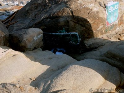 View of the upper entrance of the Cave Savr on Mount Savr in Mecca city of Saudi Arabia. The Prophet Muhammed (saaw) and his friend Abu Bakr (ra) had got shut of the Meccan enemies tracking them by hidding three days in this cave with the great help of Allah (swt). Once the unbelieving enemies had come to the entrance of the cave but they returned without entering it. When the sound of their retreating steps and voices had died away, the Prophet and Abu Bakr went to the mouth of the cave. There over the entrance a spider had woven its web. They looked through the web, and there in the hollow of a rock, even where a man might step as he entered the cave, a rock dove had made a nesting place and was sitting close as if she had eggs, with her mate perched on a ledge not for above. (Sources: Le Prophéte de l`Islam, Muhammad Hamidullah; The Life Of Prophet, Abubakr Seracudden [Martin Lings], The Hijrah). In the Holy Koran our Lord Allah said about the Savr Cave: ``If ye help not (Muhammad), (it is no matter): for Allah did indeed help him, when the unbelievers drove him out: he had no more than one companion: they two were in the Cave, and he said to his companion, ``Have no fear for Allah is with us``: then Allah sent down His peace upon him, and strengthened him with forces which ye saw not, and humbled to the depths the word of the unbelievers. But the word of Allah is exalted to the heights: for Allah is Exalted in might, Wise.`` (The Holy Koran 9:40). (The picture was taken by Mr. Mustafa one of the visitors of Artislamic.com in 2003 Ramadan.)