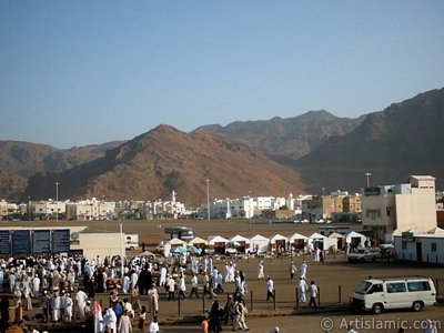 The Mounts Uhud, the field of Battle of Uhud (the second battle of the Prophet Muhammad [saaw] against unbelievers); the cemetery of the first muslims died for Islam during the Battle of Uhud (located in the left) and the pilgrims visiting these places in Mecca city of Saudi Arabia. (The picture was taken by Mr. Mustafa one of the visitors of Artislamic.com in 2003 Ramadan.)