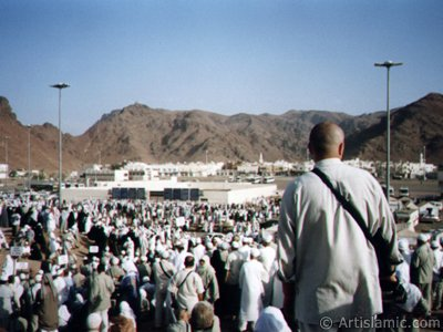 The Mounts Uhud, the field of Battle of Uhud (the second battle of the Prophet Muhammad [saaw] against unbelievers); the cemetery of the first muslims died for Islam during the Battle of Uhud (located in the middle) and the pilgrims visiting these places in Mecca city of Saudi Arabia. (The picture was taken by Mr. Mustafa one of the visitors of Artislamic.com in 2003 Hajj season.)