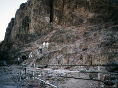 The cave located in the skirt of the Mount Uhud and the pilgrims climbing it. It is reported that when the Prophet Muhammad (saaw) was wounded during the Battle of Uhud, He had climbed into this cave and treated in it. (Sources of the event: Ibn Hisham, p.572-576; Muhammad Hamidullah, Battles of The Prophet [in Turkish: Hz. Peygamber`in Savaslari], p.70, par.106; Muhammad Hamidullah, Le Prophéte de l`Islam, par. 391.) (The picture was taken by Mr. Mustafa one of the visitors of Artislamic.com in 2003 Hajj season.)