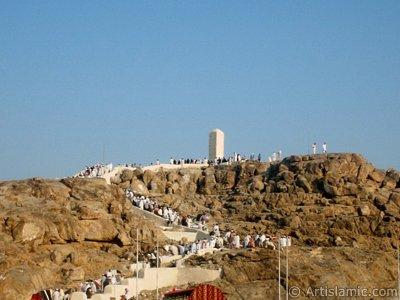 Mekke`de Arafat Meydanında bulunan Arafat Tepesi (Cebel-i Rahme) ve bu mübarek mekânları ziyaret eden hacılar. Adem Babamız ile ile Havva Annemiz`in Cennet`ten dünyaya indikten sonra burada kavuştuğu rivayet edilmektedir. (Resim 2003 yılı Ramazan`ında islamiSanat.net ziyaretçilerinden Mustafa Bey tarafından çekilmiştir.)